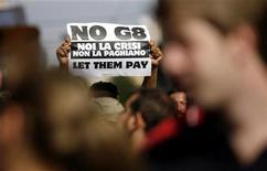 <p>Un dimostrante mostra un cartello contro il G8 a Roma. REUTERS/Alessia Pierdomenico</p>