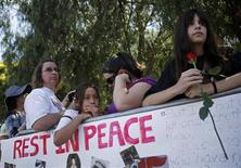 <p>Fans stand near a memorial for deceased pop star Michael Jackson outside the Jackson family home in Encino, California July 3, 2009. Jackson, the child star turned King of Pop who set the world dancing but whose musical genius was overshadowed by a bizarre lifestyle and sex scandals. Jackson was 50. REUTERS/Eric Thayer</p>