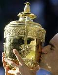 <p>Швейцарец Роджер Федерер держит в руках кубок, полученный за победу на Уимблдонском теннисном турнире 5 июля 2009 года. Швейцарец Роджер Федерер в шестой раз в своей карьере выиграл Уимблдонский теннисный турнир, в напряженном финале обыграв американца Энди Роддика со счетом 5- 7, 7-6, 7-6, 4-6, 16-14. REUTERS/Julian Finney/Pool</p>