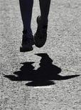 <p>An elite female runner's shadow is seen as she runs in the London Marathon April 26, 2009. REUTERS/Toby Melville</p>