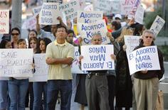 "<p>Pro-abortion advocates hold signs while marching down a street during a ""March For Life/Life Chain"" rally in Los Angeles, California in this January 22, 2006 file photo. REUTERS/Lucas Jackson/Files</p>"