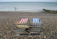 <p>People walk their dog, in light rain, on the empty beach of the south coast holiday resort town of Worthing August 23, 2007. REUTERS/Russell Boyce</p>