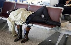 <p>Una viaggiatrice dorme in aeroporto. REUTERS/Max Rossi (ITALY)</p>