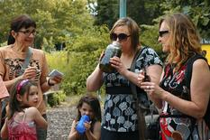 <p>Stacy Peterson (C) takes a swig from a jar of freshly brewed tea with mint and mullein, while her sister Lisa Peterson (R) watches at a community garden in Chicago July 12, 2009. REUTERS/Lisa Shumaker</p>