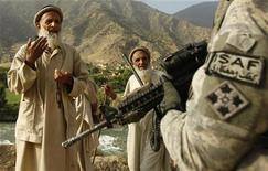 <p>Житель афганистана разговаривает с американским солдатом в провинции Кунар 30 июля 2009 года. Нынешний июль стал самым неудачным месяцем для американских войск за все время военной кампании в Афганистане. REUTERS/Tim Wimborne</p>