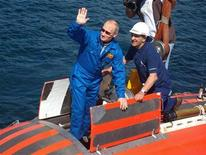 <p>El primer ministro ruso, Vladimir Putin, saluda mientras sube a bordo de un mini sumergible para explorar las profundidades del lago Baikal, el 1 de agosto del 2009. REUTERS/RIA Novosti/Kremlin/Alexei Druzhinin</p>