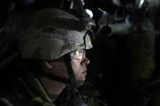 <p>A Canadian soldier sits inside an armoured vehicle during a night patrol in Kandahar city, June 13 2009. REUTERS/Jorge Silva</p>