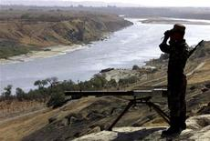 """<p>Российский пограничник осматривает в бинокль территорию Афганистана по реке Пяндж в 400 км от Душанбе 1 октября 2001 года. Таджикистан сообщил в понедельник об уничтожении боевика-исламиста в очередной кровопролитной схватке с пособниками афганского движения """"Талибан"""", помочь в войне с которым Америке обещают страны Центральной Азии и Россия. REUTERS/Stringer</p>"""