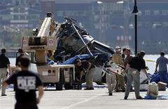 <p>Parte de un helicóptero es visto cerca del lugar donde se accidentó al lado del Río Hudson en Hoboken, Nueva Jersey, 10 ago 2009. Buzos registraban el río Hudson el lunes, buscando los últimos dos cuerpos extraviados tras la colisión de un helicóptero con un pequeño avión que ocasionó la muerte de nueve personas. Cinco turistas italianos y el piloto neozelandés del helicóptero murieron el sábado, junto al piloto estadounidense del avión, su hermano y su sobrino cuando la colisión precipitó ambas naves al río. REUTERS/Shannon Stapleton</p>