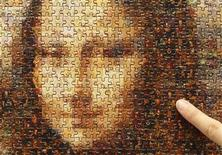 """<p>A staff of Japanese puzzle maker Beverly points at a piece of a new jigsaw puzzle """"Mona Lisa"""" displayed at the International Tokyo Toy Show 2009 in Tokyo July 16, 2009. REUTERS/Yuriko Nakao</p>"""