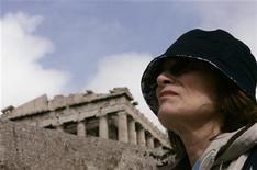 <p>Турист стоит на фоне Парфенона в Афинах 5 марта 2009 года. Томас Нтарас сидит около своего сувенирного магазинчика неподалеку от афинского Акрополя, наблюдая немногих туристов, прогуливающихся по обычно переполненным дорожкам. REUTERS/John Kolesidis</p>