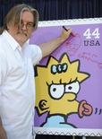 """<p>El creador y productor ejecutivo de """"Los Simpson"""", Matt Groening, firma un afiche en el lanzamiento de las primeras estampillas estadounidenses de los personajes de la serie, en Los Angeles, 7 mayo 2009. Una agencia de publicidad de Angola decidió cambiar la apariencia de Homero Simpson y su familia, sorprendiendo a los admiradores de una de las series de comedia más queridas de Estados Unidos. REUTERS/Phil McCarten</p>"""