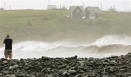 <p>A man videotapes the storm surge created by Hurricane Bill in Cow Bay, Nova Scotia, August 23, 2009. REUTERS/Paul Darrow</p>