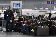 <p>An airport employee keeps an eye on luggage after a computer glitch crippled the baggage handling system at the American Airlines' Terminal 8 at New York's John F. Kennedy International Airport July 30, 2008. REUTERS/Joshua Lott</p>