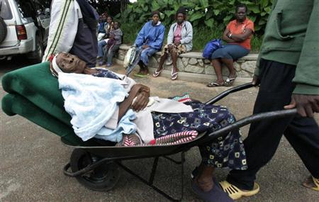 A suspected cholera patient is pushed on a wheelbarrow to a clinic in Harare, Zimbabwe, January 26, 2009. REUTERS/Philimon Bulawayo