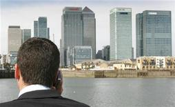 <p>A man speaks on his mobile phone while standing on a boat on the River Thames with Canary Wharf and the financial district of London seen in the background. REUTERS/Toby Melville</p>