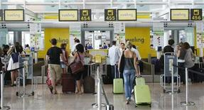 <p>Passengers queue in check-in counters in the new T-1 terminal at Barcelona's El Prat airport September 9, 2009. REUTERS/Albert Gea</p>