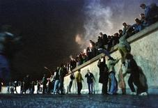 <p>East German citizens climb the Berlin Wall at the Brandenburg Gate after the opening of the border was announced early November 10, 1989. REUTERS/Herbert Knosowski</p>