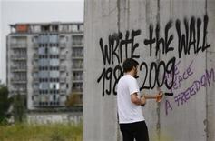 <p>Un hombre hace un graffiti sobre un segmento del Muro de Berlín, 10 ago 2009. Uno de cada siete alemanes quiere el Muro de Berlín de vuelta porque siente que estaba mejor cuando el país estaba dividido, según una encuesta de opinión publicada el miércoles, de cara al 20 aniversario de su colapso el 9 de noviembre de 1989. El sondeo de 1.002 alemanes, realizado por el instituto Forsa y publicado por la revista Stern, mostró que el 15 por ciento de los 82 millones de habitantes del país añoran los días en que había dos Alemanias. REUTERS/Thomas Peter</p>