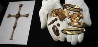 <p>Part of a hoard of Anglo-Saxon treasure named 'The Staffordshire Hoard' is held by a member of museum staff during a news conference at the Birmingham Museum and Art Gallery during a news conference in Birmingham, central England, September 24, 2009. REUTERS/Eddie Keogh</p>