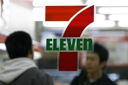 People walk behind the logo of a 7-Eleven convenience store in Tokyo, November 29, 2008. REUTERS/Stringer