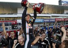 <p>O piloto de F1 Sebastian Vettel comemora vitória com seus companheiros de equipe, em Suzuka. Vettel se fia no exemplo de Kimi Raikkonen para mostrar porque Jenson Button deve se sentir inseguro em relação às suas chances de conquistar o campeonato mundial de Fórmula 1.04/10/2009.REUTERS/Issei Kato</p>