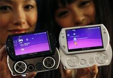 <p>Foto de archivo de unas modelos con la nueva versión de la consola de videojuegos PSP Go de Sony previo a su lanzamiento mundial en Hong Kong, 16 sep 2009. Mientras la recesión afecta a las ventas de videojuegos en las tiendas, los clientes prefieren descargarse los juegos de internet para ahorrar dinero al tiempo que se entretienen. REUTERS/Bobby Yip</p>