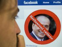 """<p>Un hombre mira el perfil en Facebook de un grupo llamado """"Uccidiamo Berlusconi"""" (""""Matemos a Berlusconi"""") en Roma, 22 oct 2009. Funcionarios italianos ordenaron una investigación de grupos de Facebook llamados """"Matemos a Berlusconi"""", diciendo que incitan al odio y podrían llevar a un ataque real hacia el primer ministro. Existen al menos tres sitios titulados en italiano """"Uccidiamo Berlusconi"""", los cuales reúnen a cerca de 16.540 miembros. Cada uno de ellos tiene una imagen de Silvio Berlusconi enmarcada en un círculo rojo y cruzada por una línea diagonal sobre la cual está escrita la frase """"Berlusconi, piérdete"""". REUTERS/Chris Helgren (IMAGENES DEL DIA)</p>"""