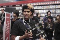 """<p>Pedro Mercado, primeiro cliente na fila para comprar uma cópia de """"Call of Duty: Modern Warfare 2"""", sorri ao ganhar de """"brinde"""" um XBox 360 em loja da GameStop em Nova York.</p>"""