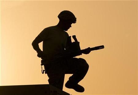 A U.S. soldier is silhouetted against sunset as he carries a grenade launcher on top of an armored vehicle on the Combat Operation Outpost (COP) McClain in Logar Province in Afghanistan July 21, 2009. REUTERS/Shamil Zhumatov