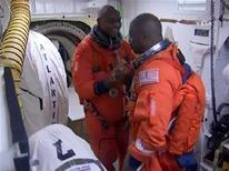 <p>Os astronautas Robert Satcher (E) e Leeland Melvin se cumprimentam enquanto se preparam para o lançamento do ônibus espacial Atlantis nesta segunda-feria (16 de novembro), no Centro Espacial Kennedy, na Flórida. Essa será uma das missões finais para equipar a Estação Espacial Internacional, de modo que a estação possa continuar em órbita muito tempo depois de os ônibus espaciais serem aposentados. REUTERS/NASA TV</p>