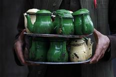 <p>A laborer carries over a dozen pots of mixed black tea to sell to shop-keepers through a market in Peshawar, located in Pakistan's North West Frontier Province on April 23, 2009. REUTERS/Ali Imam</p>