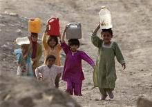 <p>Bambini afghani portano l'acqua nelle loro case. L'Afghanistan secondo l'Unicef è il paese più pericoloso al mondo per i bambini. REUTERS/Ahmad Masood</p>