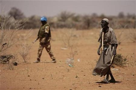 A Sudanese Man Walks While Peacekeeper From The United Nations African Union Mission In Darfur UNAMID Secures Area Outside Military Base Kor
