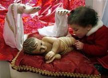 <p>A child touches a statue of Baby Jesus in the Church of the Nativity in the West Bank town of Bethlehem December 25, 2006. REUTERS/Nayef Hashlamoun</p>