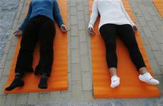 <p>People take part in a free yoga class at the Parque del Oeste in Madrid September 27, 2007. REUTERS/Susana Vera</p>