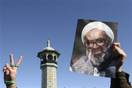 A man wearing a green band in support of the Iranian opposition holds a picture of Iran's leading dissident cleric Grand Ayatollah Hossein Ali Montazeri during Montazeri's funeral in the holy city of Qom December 21, 2009. REUTERS/Stringer/iran