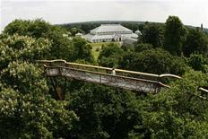 <p>A woman walks across the new Rhizotron and Xstrata Treetop walkway, with a view of the Temperate House behind, at Kew Gardens in London May 22, 2008. REUTERS/Luke MacGregor</p>