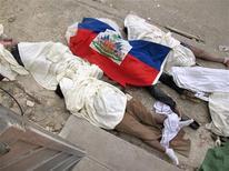 <p>Тела погибших при землетрясении, накрытые флагом Гаити на улице Порт-о-Пренса 13 января 2010 года. Испуганные мощным землетрясением гаитяне провели ночь на четверг в парках и на улицах, опасаясь новых подземных толчков. REUTERS/Joel Trimble</p>