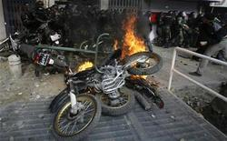 <p>An Iranian protester throws a stone at riot police as angry protesters set their motorbikes on fire during fierce clashes in central Tehran December 27, 2009. REUTERS/Stringer</p>