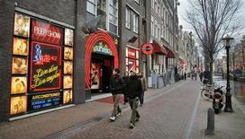 <p>Туристы гуляют по кварталу красных фонарей в Амстердаме 17 декабря 2007 года. Заместитель мэра Амстердама предложил во вторник новые меры борьбы с преступлениями на почве проституции, ограничив время работы борделей и повысив минимальный возраст для занятия древнейшей профессией с 18 до 23 лет. REUTERS/Koen van Weel</p>