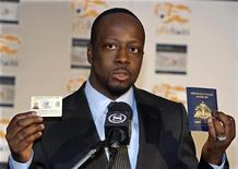 """<p>Музыкант Уайклиф Жан, уроженец Гаити, держит вид на жительство в США и паспорт Гаити на пресс-конференции в Нью-Йорке 18 января 2010 года. Благотворительный телемарафон """"Надежда для Гаити"""", проведенный актером Джорджем Клуни и рэпером Уайклифом Жаном помог собрать для жертв землетрясения $57 миллионов. REUTERS/Ray Stubblebine</p>"""