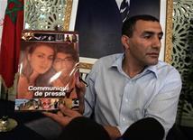 <p>Олимпийский чемпион 1992 года Марокко Халид Сках показывает репортерам фотографию своих детей, Рабат 5 августа 2009 года. Норвежские спецназовцы помогли матери вернуть двух детей из Марокко, которые находились в доме ее бывшего мужа - олимпийского чемпиона по плаванию. REUTERS/Rafael Marchante</p>