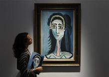 """<p>Funcionária posa em frente ao quadro """"Tete de femme"""" de Picasso, em Londres. Pablo Picasso mostrou mais uma vez seu enorme valor para colecionadores ricos quando um retrato feito pelo artista de sua segunda mulher, Jacqueline, alcançou o maior valor no leilão de arte impressionista e moderna da Christie's em Londres, na terça-feira.20/01/2010.REUTERS/Stefan Wermuth</p>"""