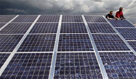 Workers set up photovoltaic panels in the solar park project in Goettelborn, near the western German city of Saarbruecken, June 21, 2004. REUTERS/Vincent Kessler