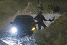 <p>Водитель расчищает лопатой снежный занос, Вашингтон, 9 февраля 2010 года. Сильнейшие снегопады вновь обрушились на восточное побережье США от Вашингтона до Нью- Йорка. REUTERS/Jason Reed</p>