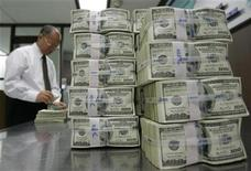 <p>An employee of the Korea Exchange Bank works next to stacks of one hundred dollar notes at the bank's headquarters in Seoul February 3, 2009. REUTERS/Jo Yong-Hak</p>