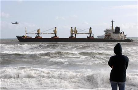 A woman looks out over the Turkish bulk carrier MV SELI 1, carrying a 30,000 tonne coal cargo, that ran aground near Cape Town, September 8, 2009. REUTERS/Mike Hutchings
