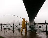 <p>Мужчина ловит рыбу во время дождя в Сиднее 25 января 2006 года. Жители небольшого австралийского городка Ладжаману недолго удивлялись, когда на их головы обрушился рыбный дождь. Они достали ведра и за два дня подобного катаклизма успели собрать приличный улов. REUTERS/Will Burgess</p>