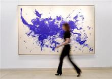 "<p>An employee poses for photographers as she walks past the ""ANT 93, Le Buffle (The Buffalo)"" painting from 1960-61 by French artist Yves Klein at Christie's auction house in London March 4, 2010. REUTERS/Suzanne Plunkett</p>"